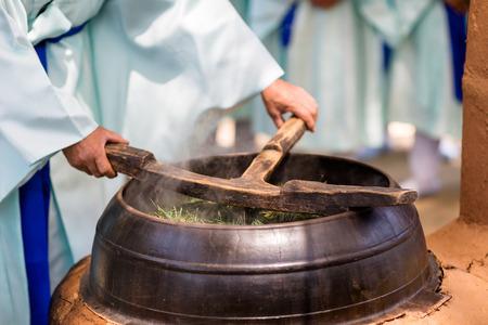 Korean holy rice wine-Korean man brewing holy rice wine with cauldron in kiln