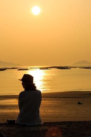 천천히 도시 섬 - 석양 모래 해변에 앉아있는 여자의 실루엣
