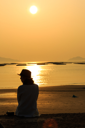 Slow city island-Silhouette of a girl sitting down on the sand beach at sunset