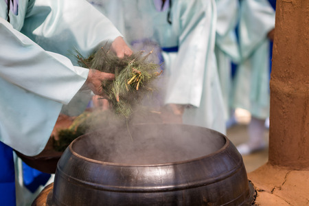 Korean holy rice wine-Korean man brewing holy rice wine with cauldron in kiln