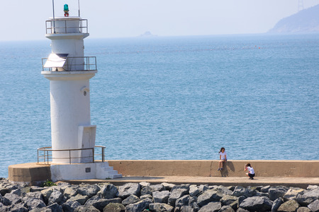 Slow city island-Two Korean girls taking pictures by the light house