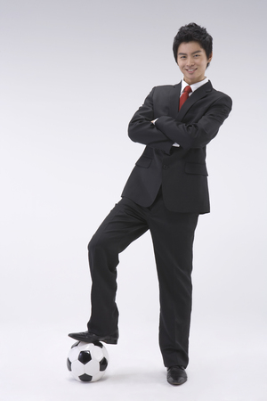 Asian man in suit posing in a studio with a soccerfootball ball