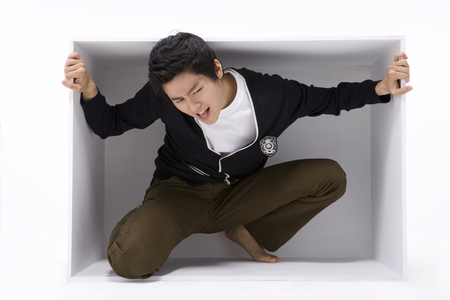 Asian man posing as sitting in a white box
