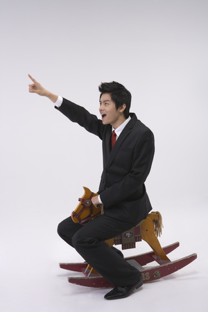 Asian man in suit posing in a studio riding a wooden horse