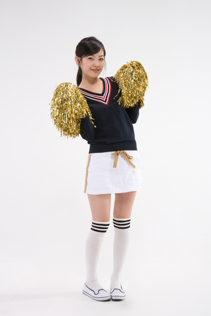 Asian girl teenager in school gym unifrom posing in a studio with cheerleading dusker