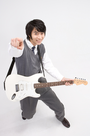 Asian male teenager in school unifrom posing in a studio with guitar Stock Photo