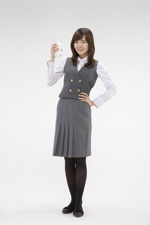 Asian female student in school unifrom posing in a studio with a glass of milk Stock Photo
