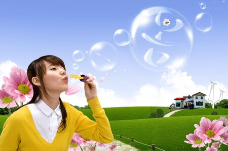 Female Asian making soap bubbles to the green grass field
