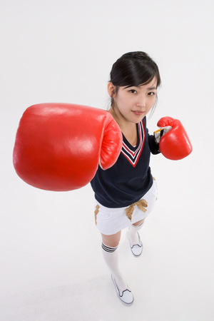 Asian girl teenager in school gym unifrom posing in a studio with boxing gloves