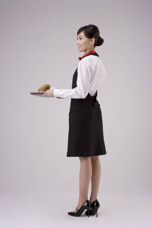 Asian female waitress posing in a studio with a tray of bagels and coffee