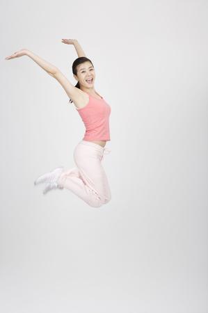 若いアジアのジャンプ/跳躍スタジオでヨガのスーツの女性 写真素材