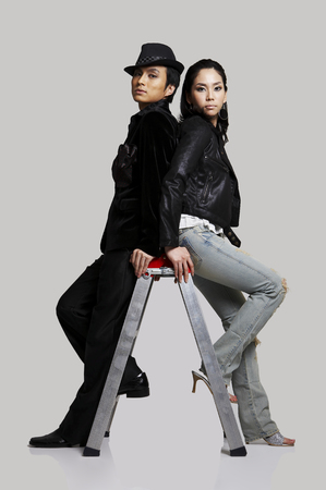 Asian male and female artists in black jackets posing in a studio