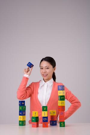 Kindergarten teacher posing in a studio with letter blocks