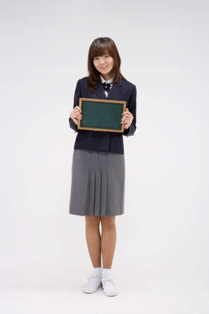 Asian female student in school unifrom posing in a studio with an empty black board