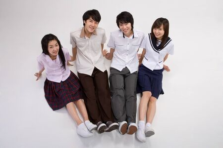 Four Asian teenagers in school uniforms posing in a studio as sitting down