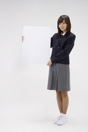 Asian female student in school unifrom posing in a studio with an empty white board