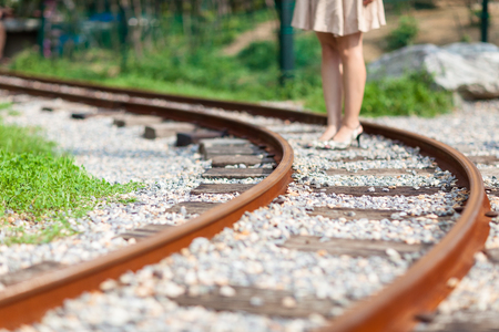 Isolated shot of a womans legs standing on a rail tracks