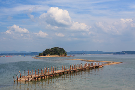 Scenery of wooden bridge linking to rock island at low tide Stock Photo