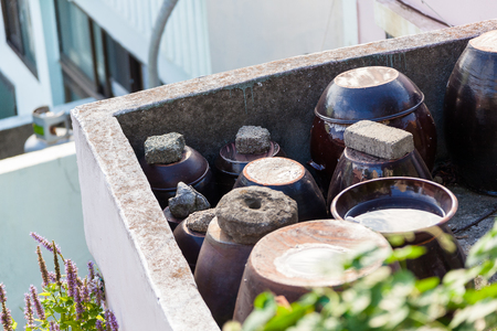 Earthenwear waterjars placed together on the corner of rooftop