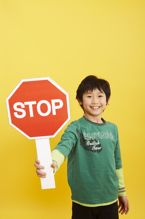 Young Asian boy posing in a studio with stop sign