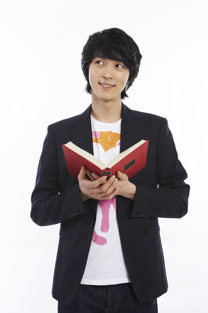 Young male Asian in black jacket posing in a studio with a book Stock Photo