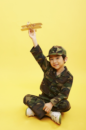 Young Asian boy wearing army uniform posing in a studio with toy airplane