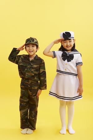 niños actuando: Joven asiático y niña en uniformes militares posando en un estudio con saludos de mano Foto de archivo