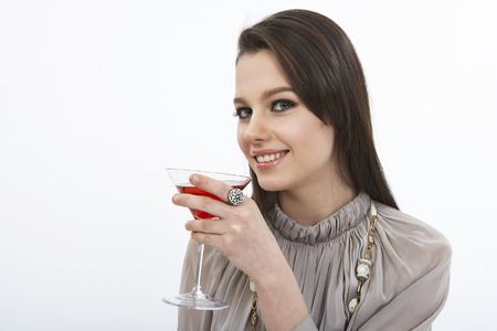 Close up shot of woman in dress posing in a studio with cocktail