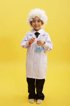 Young Asian boy dressed up like old silver hair scientist posing in a studio
