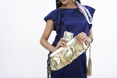 Woman in dress posing in a studio with a purse