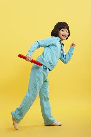 Jong Aziatisch meisje in opleidingskostuums die in een studio met relaisknuppel stellen