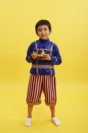 Young Asian boy wearing aladdin costume posing in a studio with a lamp Stock Photo