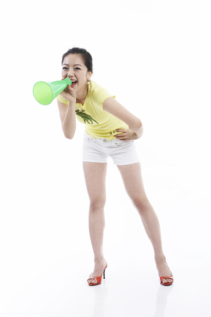 loudspeaker: Young female Asian in summer outfit posing in a studio with cheering horn