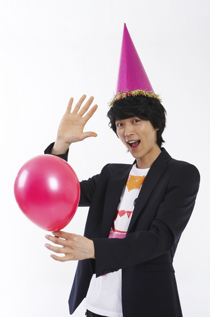 Young male Asian in black jacket posing in a studio with balloon