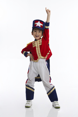 Young Asian boy wearing military marching band uniform posing in a studio