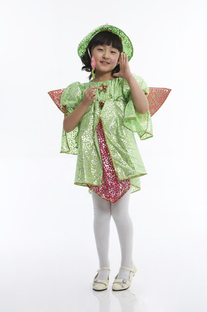 Young Asian girl wearing fairy costume posing in a studio with a magic stick