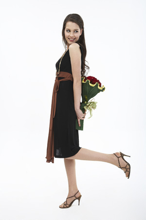 Woman in dress posing in a studio with a bouquet of flower