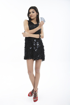 Woman in dress posing in a studio with credit card