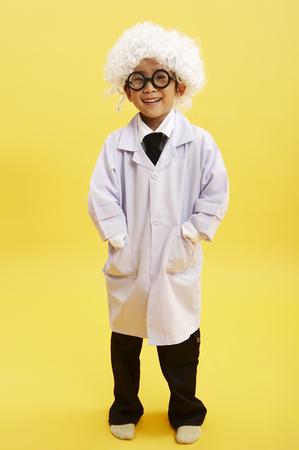 niños actuando: Joven muchacho asiático disfrazado de viejo científico de cabello plateado posando en un estudio