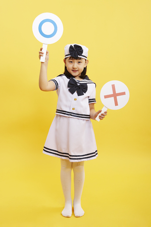 Young Asian girl in marine uniform posing in a studio with OX signs
