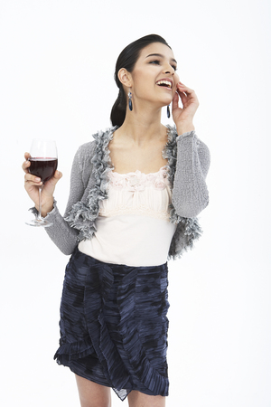 Fashionable woman in formal look posing in a studio with wine