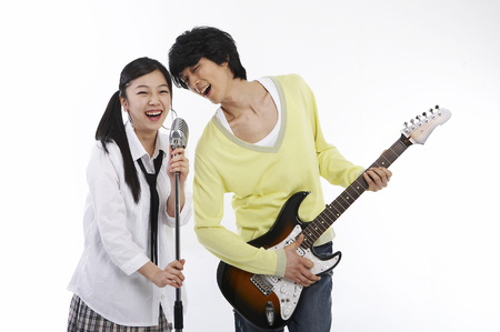 Young Asian fashionable couple posing in a studio with guitar and microphone Stock Photo