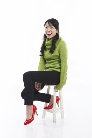 Young female Asian posing in a studio as sitting on chair