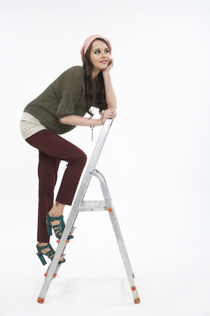 Woman in fall fashion posing in a studio with ladder