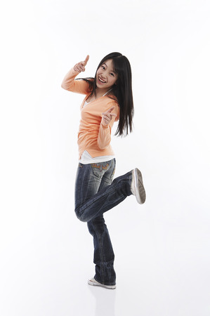 Young female Asian in orange shirt posing in a studio