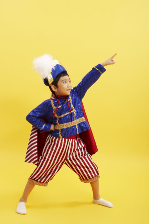 Young Asian boy wearing a prince costume posing in a studio