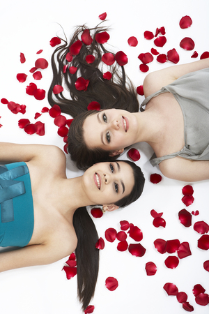 Two fashionable women posing together in a studio as lying on rose petals Stock Photo