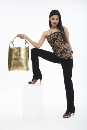 Woman in leopard top posing in a studio with purse