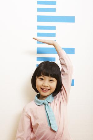 Jong Aziatisch meisje dat haar hoogte meet