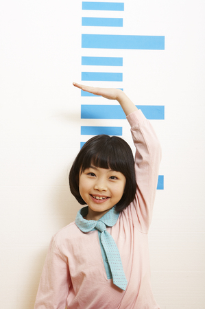 Young Asian girl measuring her height
